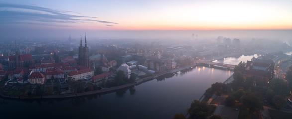 Widok z lotu ptaka na smog nad budzącym się miastem o świcie, w dali budynki okryte mgłą i smogiem - Wrocław, Polska - fototapety na wymiar