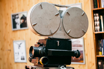 Photo of an old movie camera on a wooden background in a film studio.