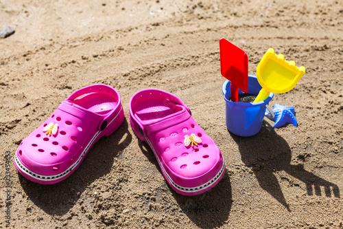 c37d687655bc2a Pink beach crocs and blue sand toys on sandy beach.Beach flip flops in the