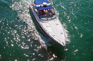 Overhead view of a white motorboat with blue canvas canopy