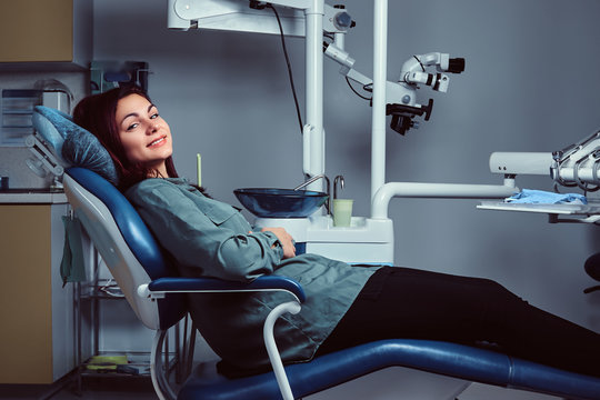Young woman sitting in a chair in a dentist office.
