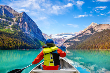 Photo sur cadre textile Canada Boy Canoeing on Lake Louise in Banff National Park Canada