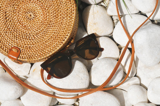 Straw bag with sunglasses on pebble stones
