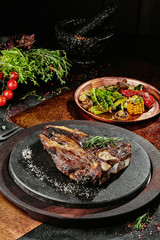 Fermented steak. T-Bone steak serving with grilled vegetables on a black round plate on a background of greens, spices and vegetables, on a copper sheet. close up