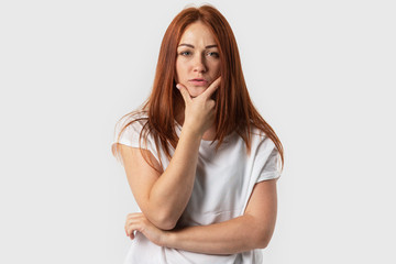 Young red-haired girl confidently looks into the camera. Isolated on gray background.