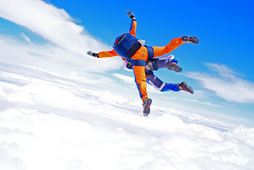 Sky diving tandem above the clouds