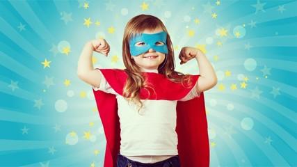 Portrait of  beautiful little girl in superhero costume on sky
