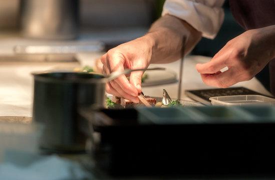 Restaurant chef preparing a plate under a warm light