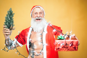 Happy tattoo hipster santa claus equiped with white lights giving christmas gifts - Trendy beard senior wearing xmas clothes and holding presents - Celebration and holidays concept