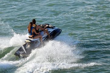 Couple running waves on speeding jet ski.