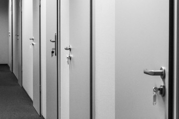 Long corridor in an office building. Many closed doors. Doors with keys in locks. Office theme. Work schedule. Workplace office workers.