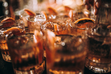 A close up shot of whisky based cocktails with ice cubes on the bar. Fine alcohol, beverage and whisky concept.