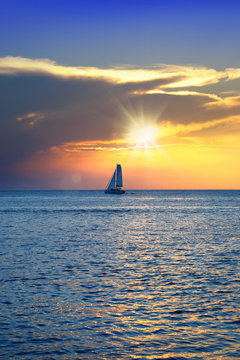 Colorful seascape image with shiny sea and sailboat over cloudy sky and sun during sunset in Cozumel, Mexico