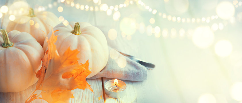 Thanksgiving background. Holiday scene. Wooden table, decorated with pumpkins, autumn leaves and candles