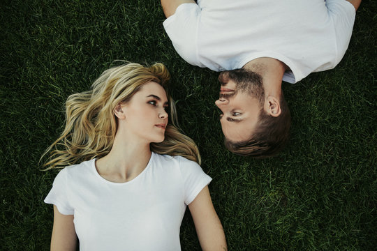 Top view of happy young woman is lying on lawn and looking at her boyfriend with tenderness. They wearing white t-shirts