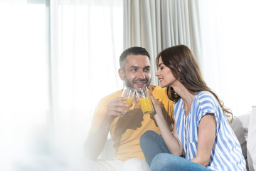 Happy man talking with cute woman while drinking orange juice in their apartment. Copy space in left side