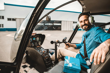 Positive emotional young man in colorful clothes sitting in the helicopter cabin and putting one hand on the seat while smiling and looking at you