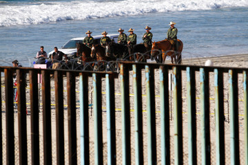 U.S. border patrol stand behind the border fence between Mexico and the United States, as seen from Tijuana