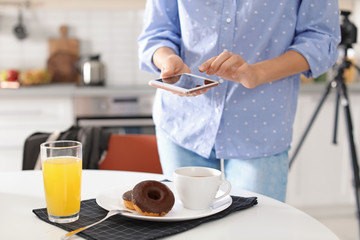 Food blogger taking photo of breakfast in kitchen