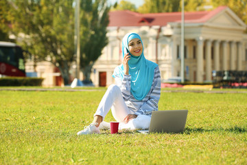 Muslim woman in hijab with laptop talking on phone outdoors