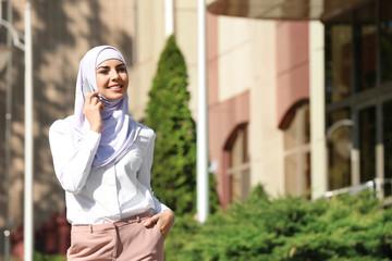 Muslim woman in hijab talking on phone outdoors