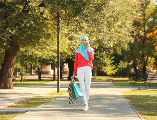 Muslim woman with shopping bags talking on phone in park