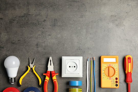 Electrician's tools and space for text on gray background, flat lay