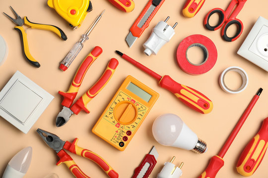 Flat lay composition with electrician's tools on color background