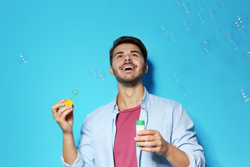 Young man blowing soap bubbles on color background