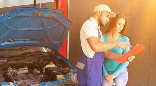 Auto mechanic and female customer in garage