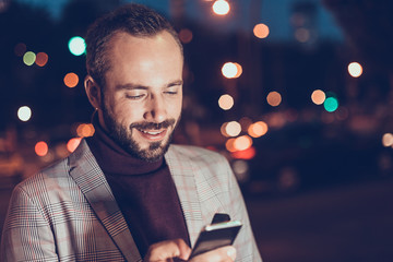 Positive bearded young man feeling glad and smiling while reading messages on the screen of his modern smartphone