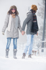 Young couple walking in snow in nature