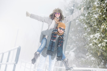 Young couple playing in snow in nature