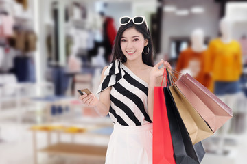 happy woman holding credit card and shopping bag at mall