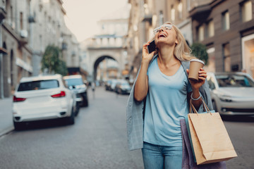 Waist up portrait of cheerful middle-aged lady in glasses enjoying phone conversation. She is holding cup of coffee and shopping bags while standing on the street