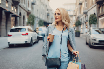 Waist up portrait of beautiful middle-aged lady in glasses holding cup of coffee and shopping bags. She is looking away and smiling