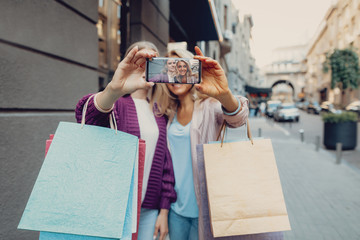 Beautiful middle-aged lady and her daughter taking photo with smartphone while holding shopping bags. Focus on phone display with women photo