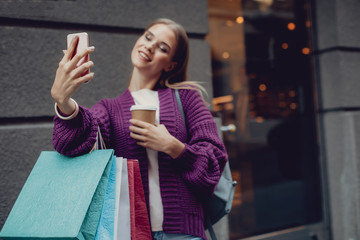 Portrait of smiling girl taking picture with smartphone while holding shopping bags and cup of coffee. Focus on lady hand with cellphone