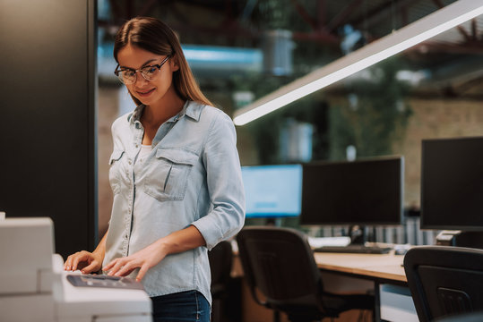 Waist up portrait of charming woman standing near photocopier and smiling. Desk with computers on blurred background