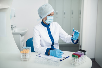 Professional laboratory investigations in healthcare system. Waist up portrait of female facility expert making notes while looking at test tube of blood