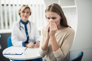 Concept of professional consultation and disease. Waist up portrait of young female patient blowing nose while consulting in medical office