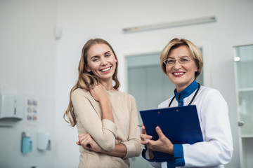 Concept of professional inspiration in healthcare system. Waist up portrait of cheerful female doctor with patient standing in medical office