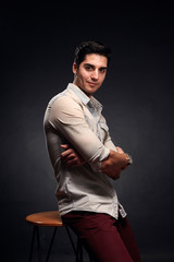 one young handsome man, handsome model, 20-29 years old, posing in studio, photo shoot. black background. casual clothes. wearing jeans shirt.