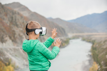 Little boy in virtual reality glasses stands on the background of the mountains