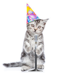 Kitten in birthday hat singing with microphone a karaoke song. isolated on white background