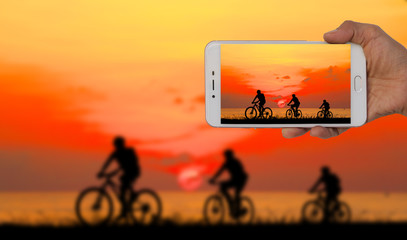 Tourist taking a picture of blur image of group friend  and bike relaxing on red sky  background.