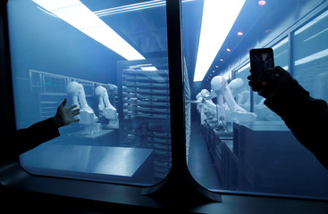A customer takes a picture as robotic arms collect pre-packaged dishes from a cold storage, done according to the diners' orders, at Haidilao's new artificial intelligence hotpot restaurant in Beijing