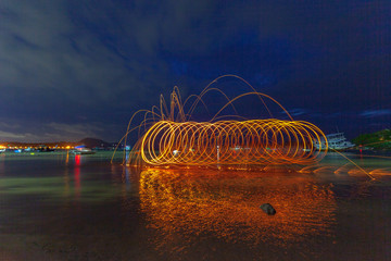 reflection of spark fire swirl from steel wool with long exposure speed motion abstract at sunrise in the sea..