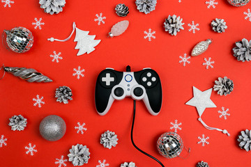 Joystick with Christmas decorations on red background.