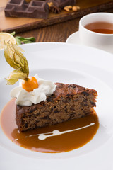 Slice of chocolate cake served with cupt tea and mint